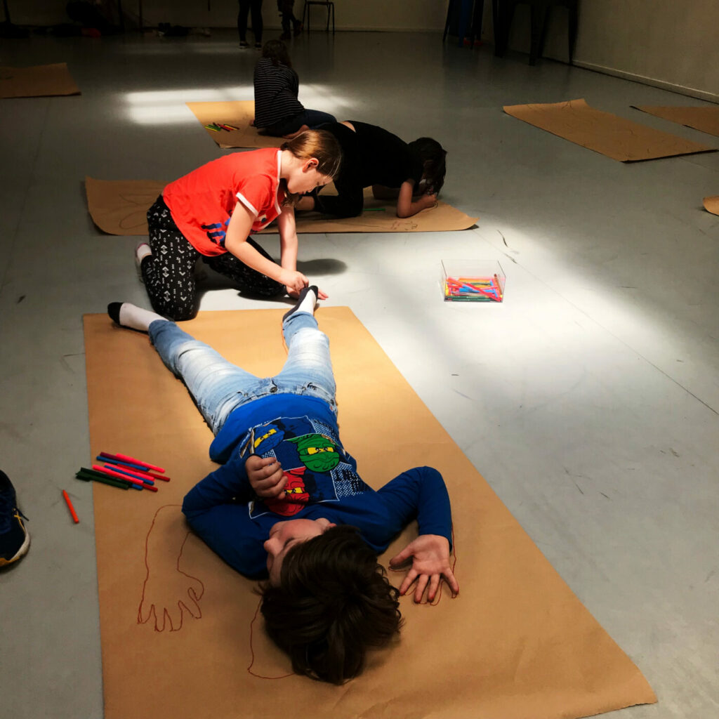 two young people in casual clothes, one laying down on paper the other one tracing them