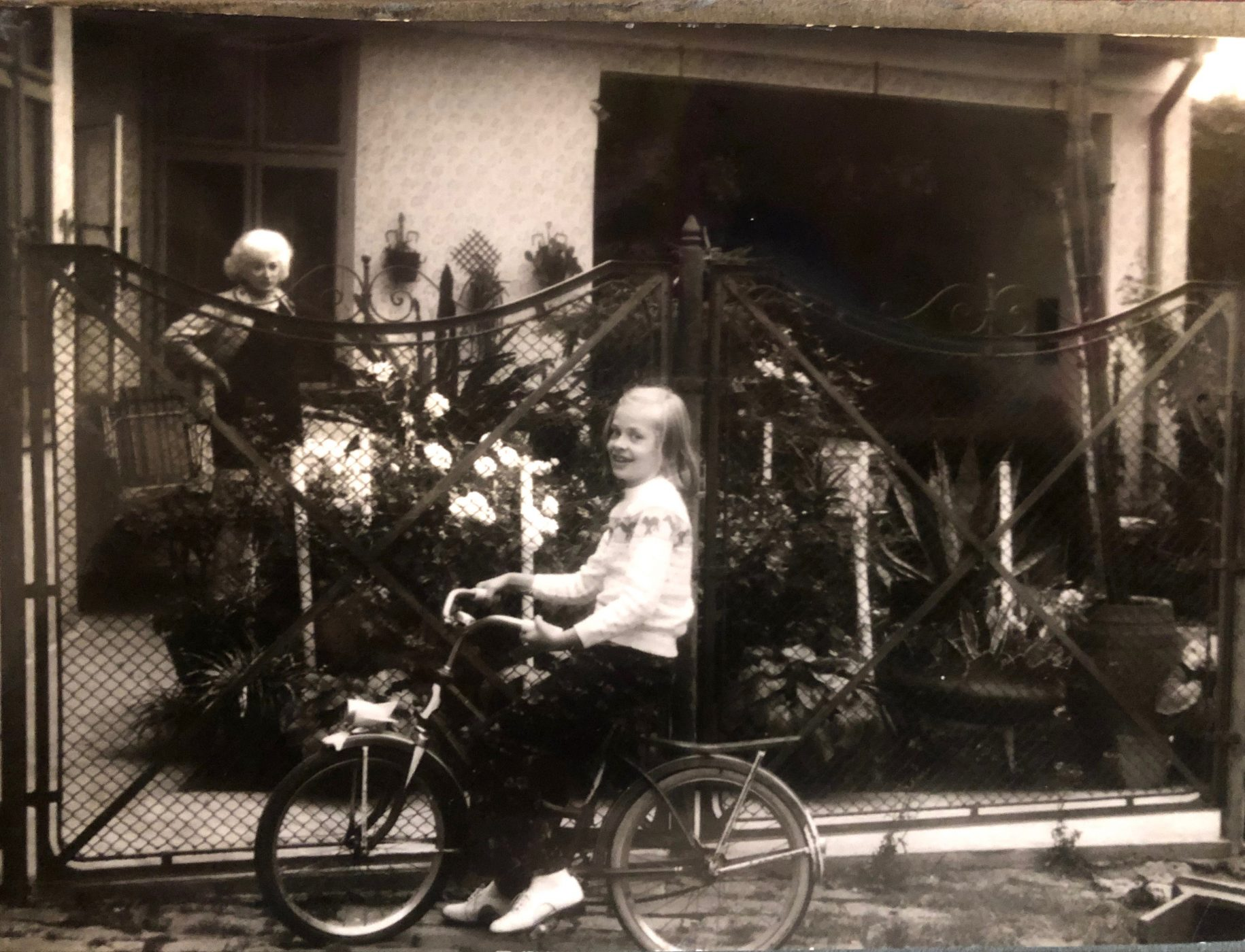 sepia photo of young blond girl smiling on a bicycle with mother in background hands on hips