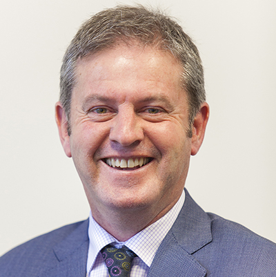 Steve Bradby. White Middle Aged Man with short grey hair smiling and facing the camera. He is wearing a Light Blue suit, a white shirt with blue checked lines, and a Black Tie with small colourful circles