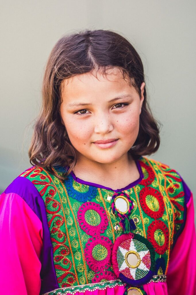 young girl with white skin, brown hair and a pink and colourful patterned dress