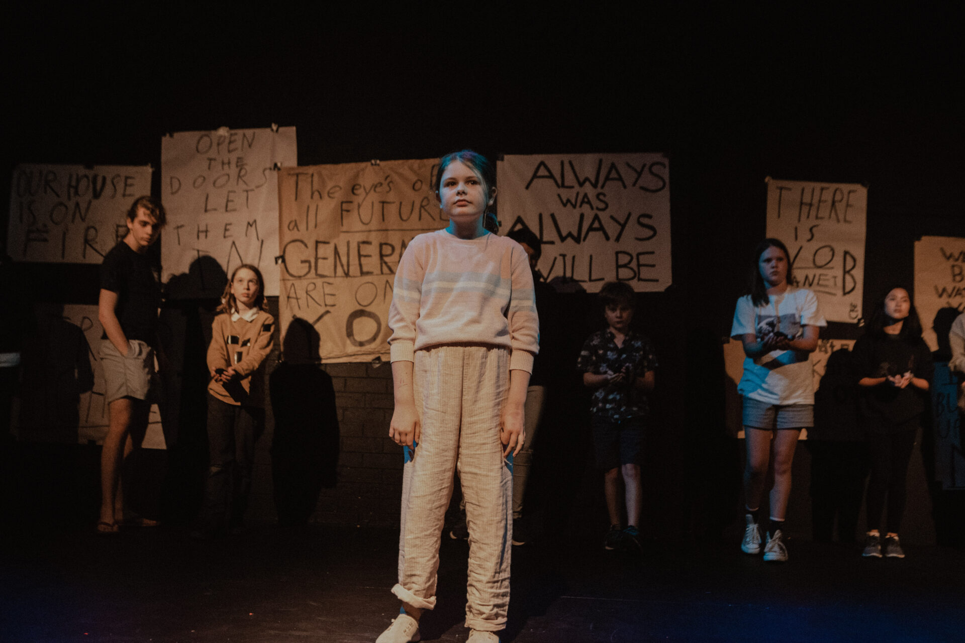 Young girl in white infront of crowd of young people and poster paper with words on them all staring at an audience under light