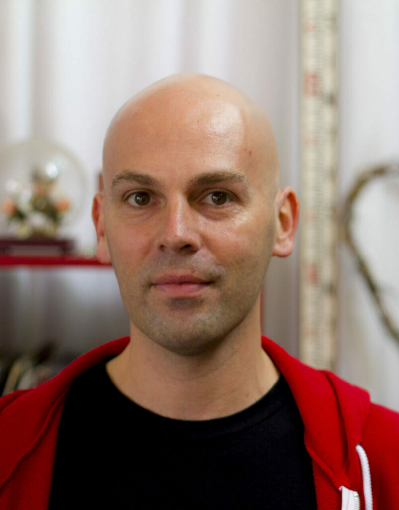 Daniel Tobias. A White man with a shaved head. He is looking to camera with a neutral expression. He is wearing a black t-shirt with a red zip up hoodie.