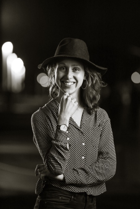 young white woman with long hair smiling at camera with hand on chin, one hand across waist. black and white photo with spotted shirt, long hair and black hat. smiling at the camera