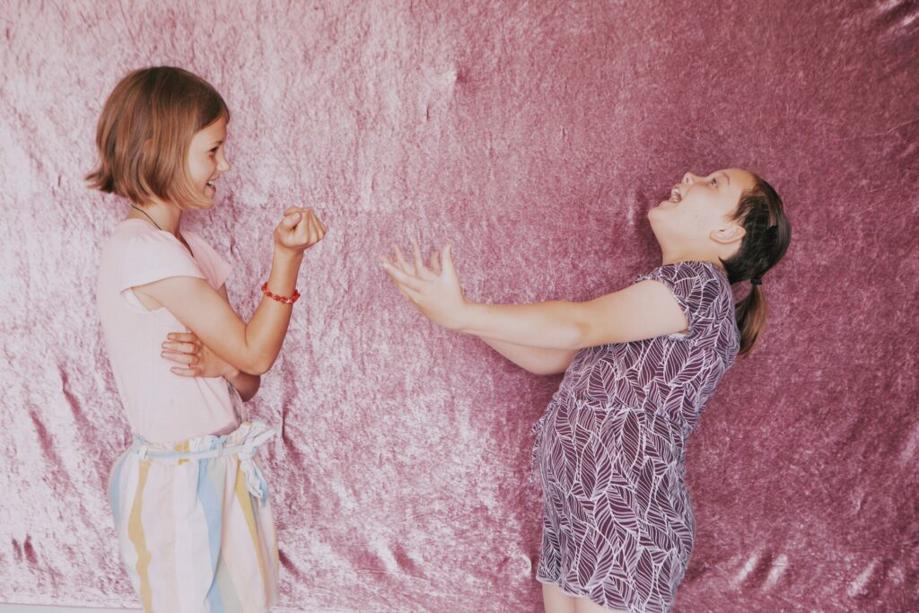 Two girls stand in front of pink velvet making gestures
