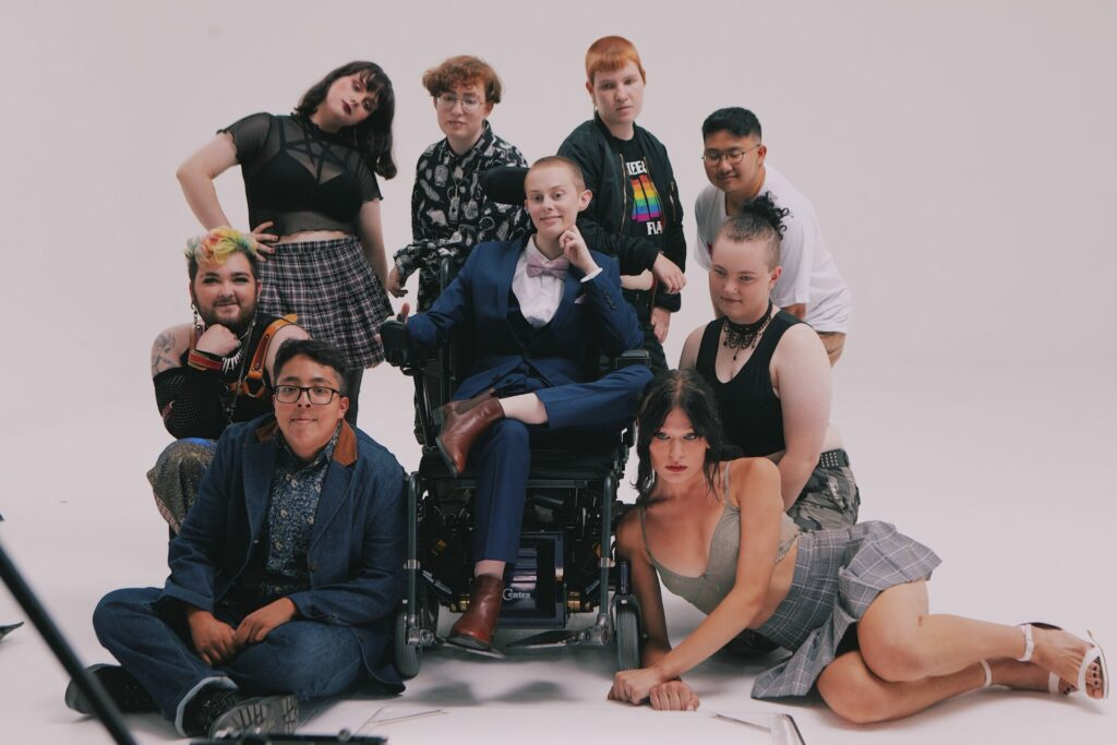 Nine People of various gender presentations stand in front of a cream white background. Two are on the floow, two are kneeling, four are standing, and one is on an motorised wheelchair.