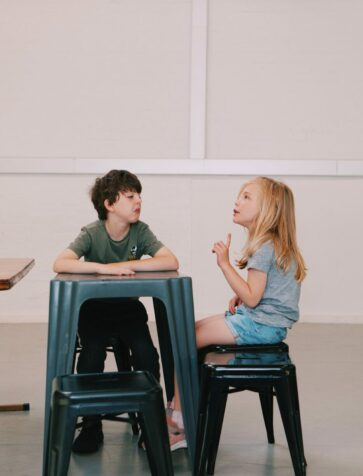 A young boy and girl sit at a table pulling funny faces